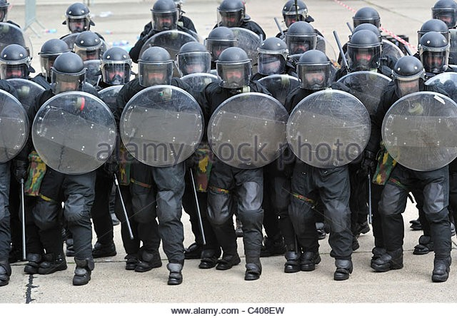 riot-squad-police-officers-forming-a-protective-barrier-with-riot-c408ew